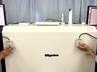 大型のツインモニターX線検針機を使用して検針している様子 1